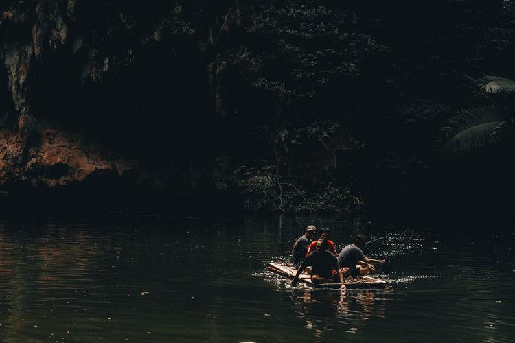 Men sitting on raft in lake