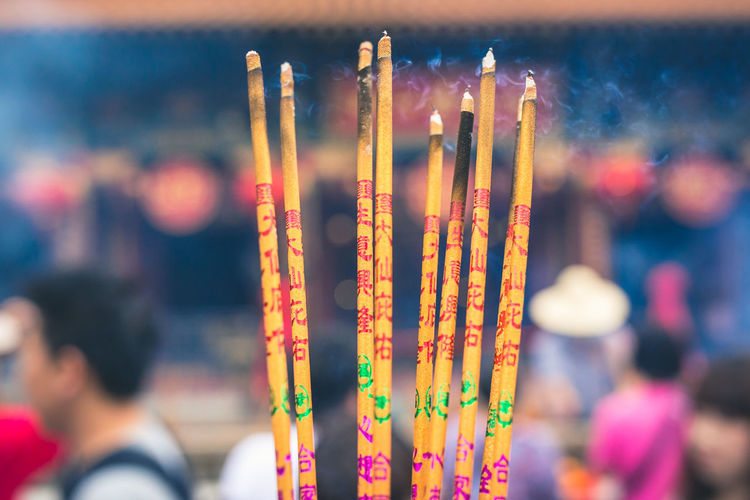 Close-up of incenses burning outside temple