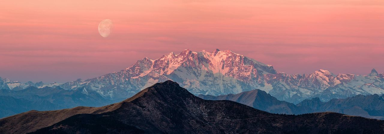 Panoramic view of monte rosa against orange sky in winter