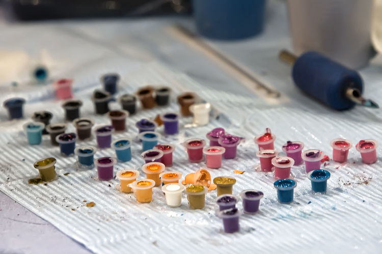 Close-up of multi colored tattoo ink pots