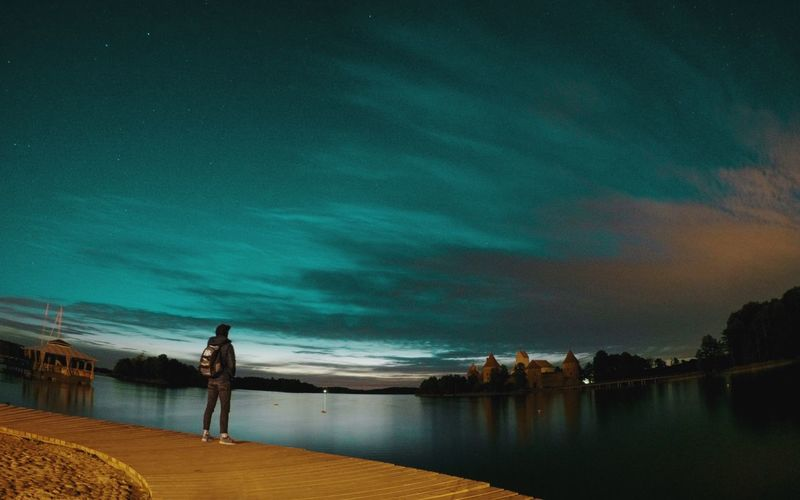 Rear view of man standing on boardwalk against trakai island castle at night