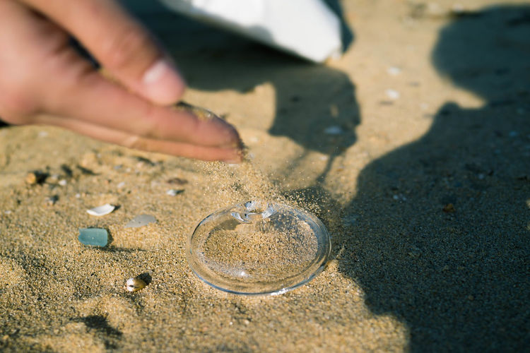 Cropped hand of person putting sand on glass container