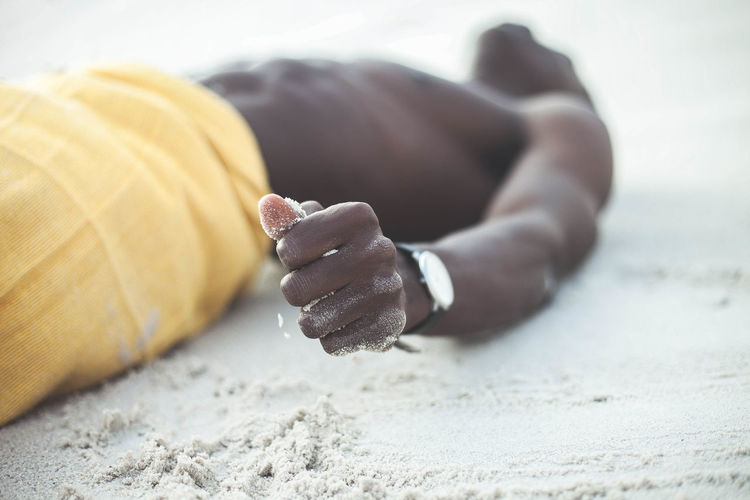 Close-up of hand on sand at beach