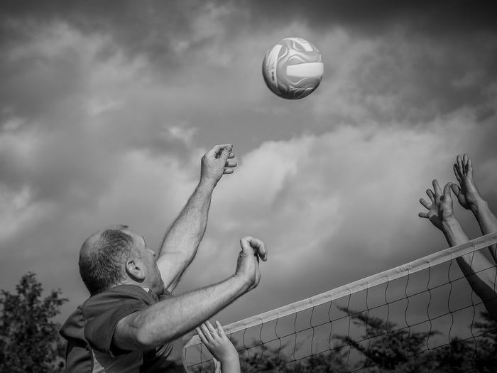 Low angle view of man playing volleyball against sky