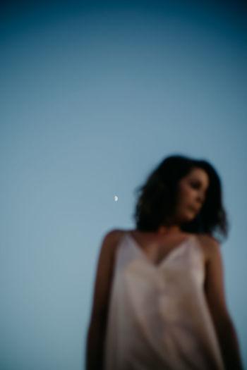 Woman looking away against blue sky