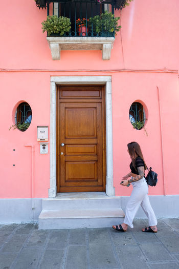 woman walking along street in front of pink wall Young Adult Italy Venice Venice, Italy Pink Color Pink Woman Women colour of life Pop Of Color Burano Burano, Italy Entrance Door Full Length One Person Architecture Adult Day Building Exterior Building Real People Lifestyles Standing Sitting Young Women Outdoors Fashion Walking Walking Around Front Door