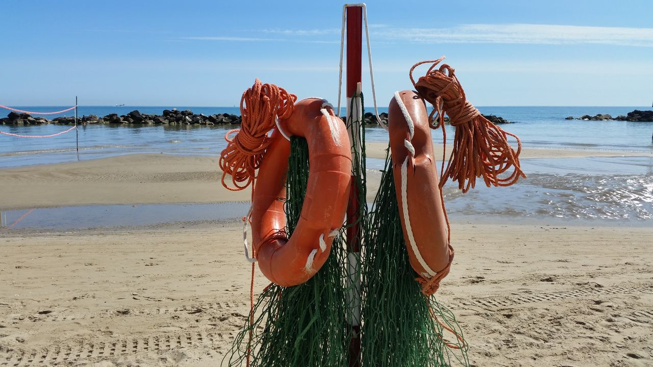 Rescue Equipment Hanging On Pole At Beach Against Sky