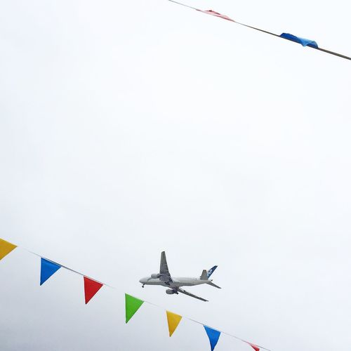 Low angle view of colorful bunting and airplane against clear sky