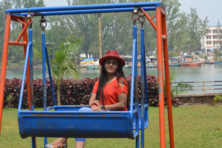 Portrait Of Young Woman Sitting On Swing At Park