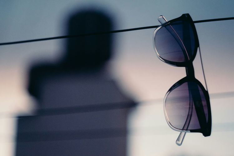 Close-Up Of Sunglasses Hanging From Cable With Person In Background Against Sky