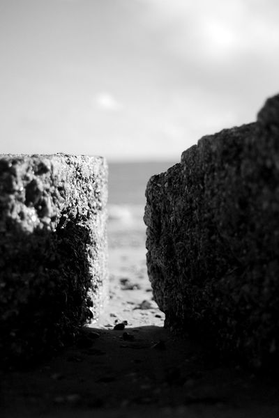 Sea Between The Blocks Beach Black And White Blackandwhite Close-up Concrete Focus On Foreground Land Outdoors Rock Rock - Object Sea Selective Focus Sky Solid Tranquil Scene Tranquility Water