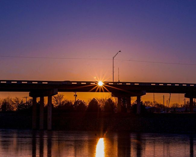 Silhouette bridge over river against clear sky at sunset
