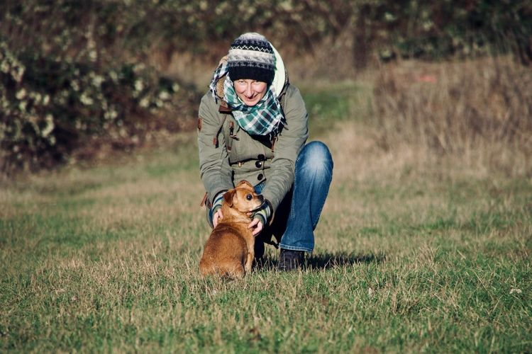 Portrait of smiling woman playing with dog on grassy field