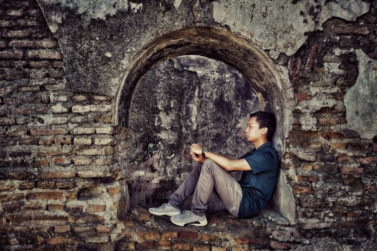 Side view of man sitting against wall