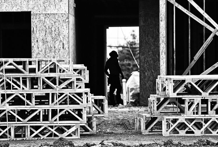 Rear view of man standing on staircase of abandoned building