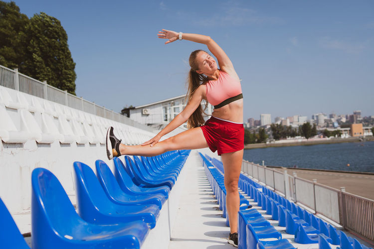 Woman stretching while standing outdoors