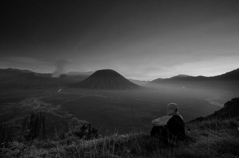 Man sitting on landscape against sky
