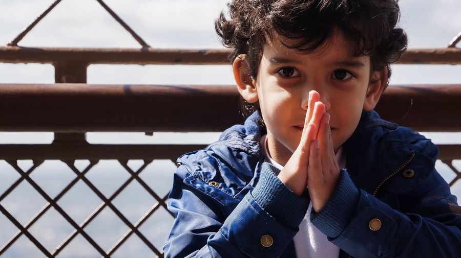 Close-up portrait of boy with hands clasped against fence