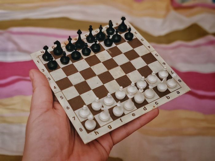 High angle view of person playing guitar on chess board