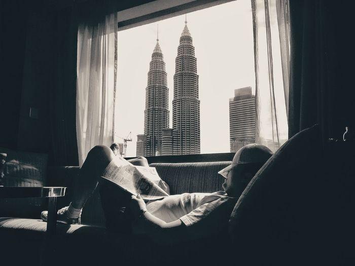 Man Lying On Sofa With View Of Petronas Towers Seen Through Window