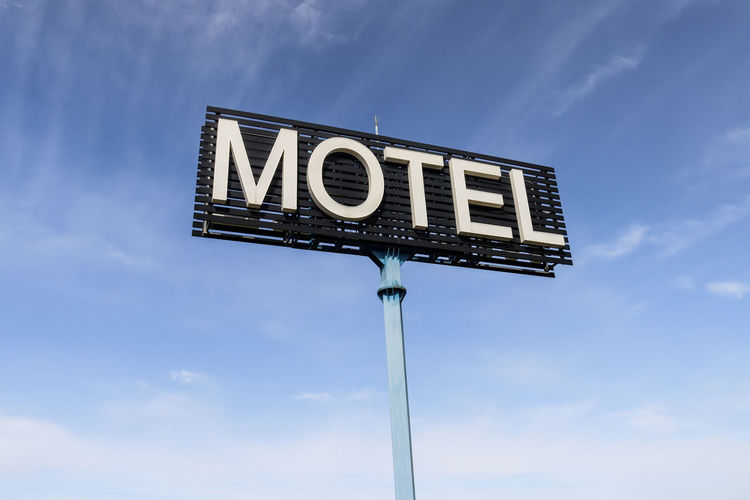 Low Angle View Sign Communication Text Sky Cloud - Sky Western Script Blue No People Nature Road Sign Day Information Capital Letter Outdoors Information Sign Symbol Road Guidance Arrow Symbol Motel Hotel