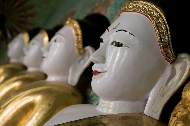 Close-up of buddha statues in temple