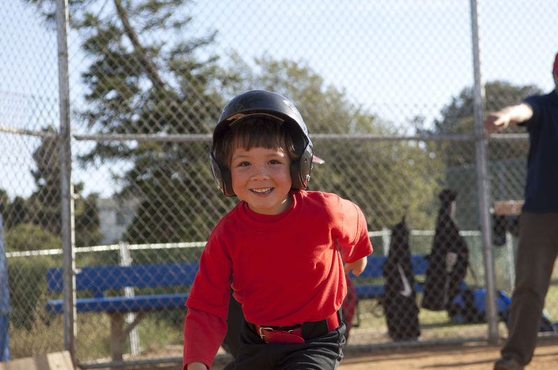 Portrait of smiling boy standing by fence