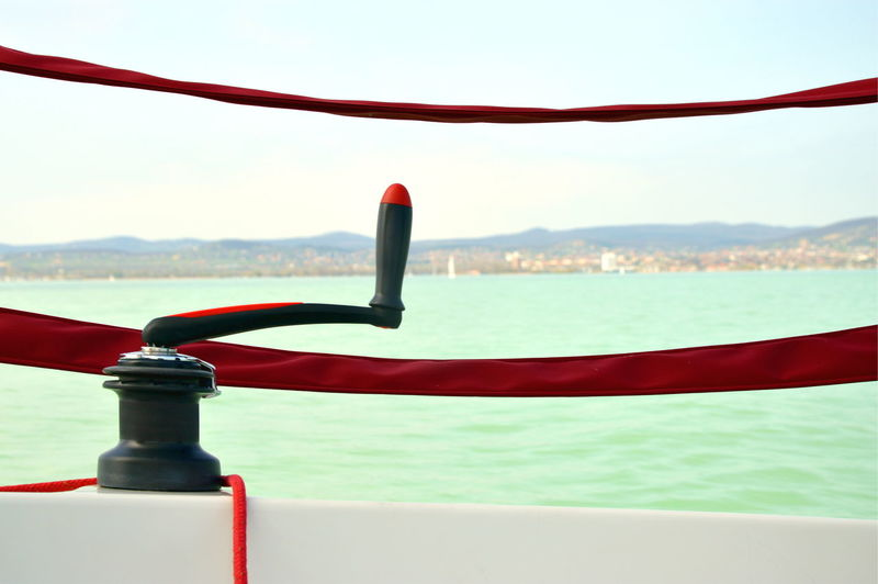 Close-up of rope handle on boat in sea against sky