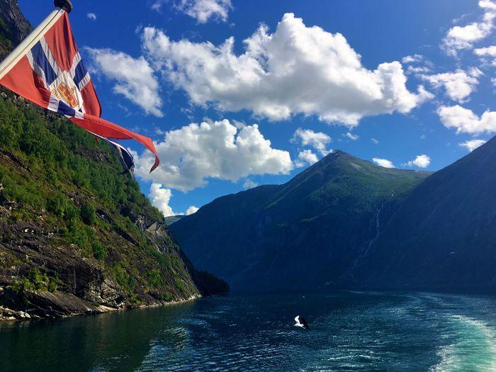 Norwegian flag on mountain at geirangerfjord