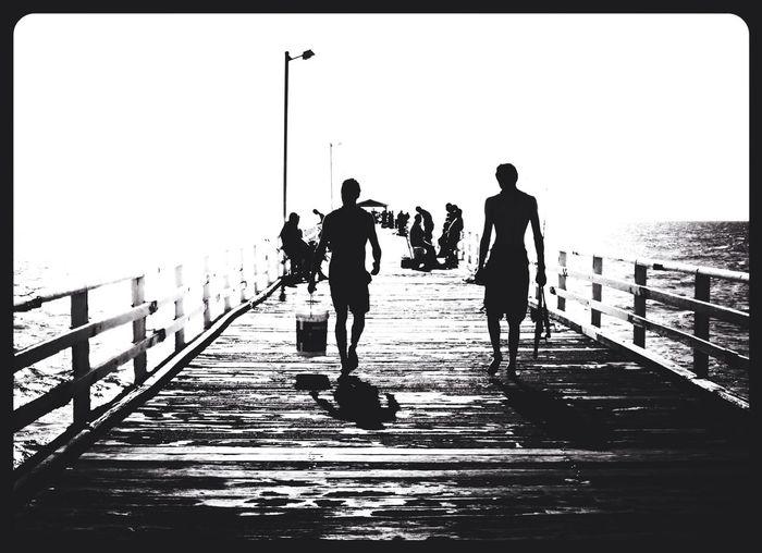Man walking on pier at sea