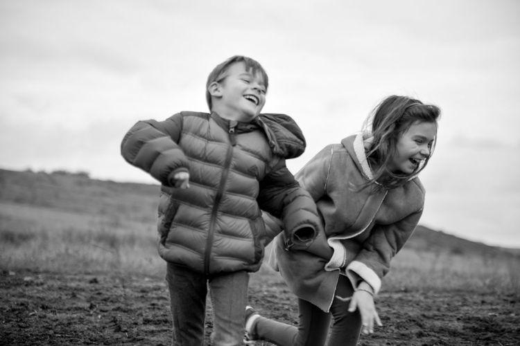 Happy siblings on field against sky