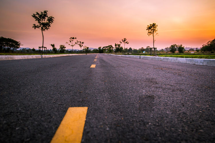 Surface level of road against sky at sunset