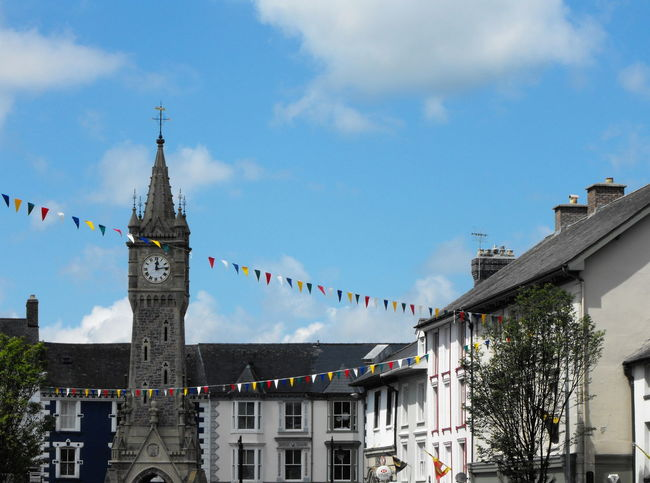 A clock tower Building Exterior Built Structure Architecture Building Sky Flag Bunting Religion Decoration Nature Spirituality Place Of Worship Belief Day Cloud - Sky Celebration No People Travel Destinations City Outdoors Spire  Clock Tower Flags Wales UK Town Centre