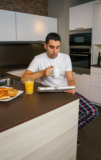 Young man having breakfast in the kitchen and reading the newspaper Vertical Comfortable Cozy Unmarried Single Enjoying Relax Unhealthy Healthy Sitting One News Modern Croissant Serious Portrait Biscuits Orange Juice  Coffee Indoor Alone Real Clean Adult Drink Young Concentrated Journal Morning Sunday Reading People Concerned Handsome Male Lifestyle Husband Caucasian Home Kitchen Tranquility Interested Newspaper Looking Breakfast Pajama Man