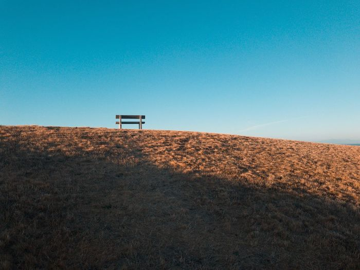 Low angle view of bench on land against clear blue sky