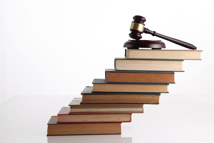 Close-Up Of Stacked Books With Gavel Against White Background