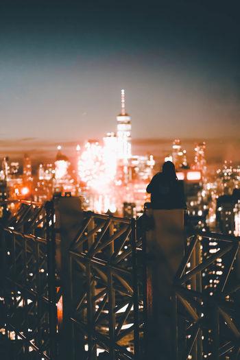 Person looking illuminated cityscape at night