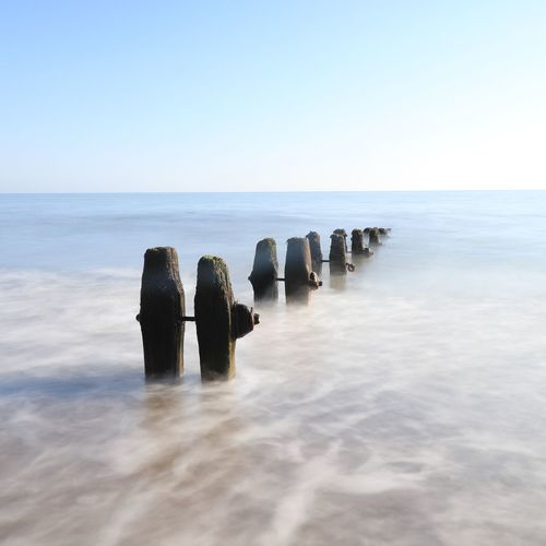 groynes and long exposure Water Sea Horizon Beach Groyne Clear Sky Sunlight Sky Horizon Over Water Landscape Seascape Old Ruin Wooden Post Ruined Coast Bad Condition Weathered Tide Shore Low Tide Ocean Ancient Wave Civilization