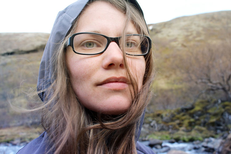 Close-up portrait of woman wearing hooded shirt while standing against mountain