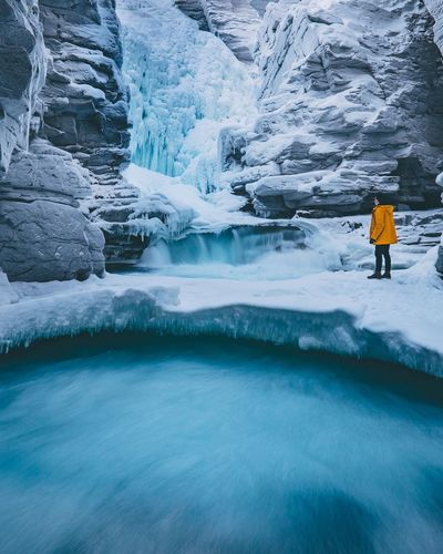 Side view of young man standing by frozen waterfall