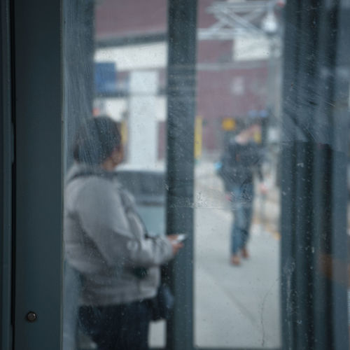 Side view of person at bus stop seen through window