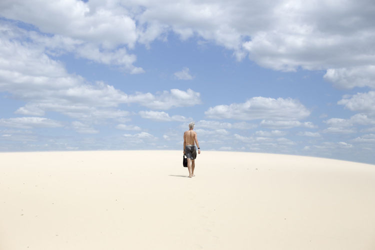 Rear view of man walking on sand