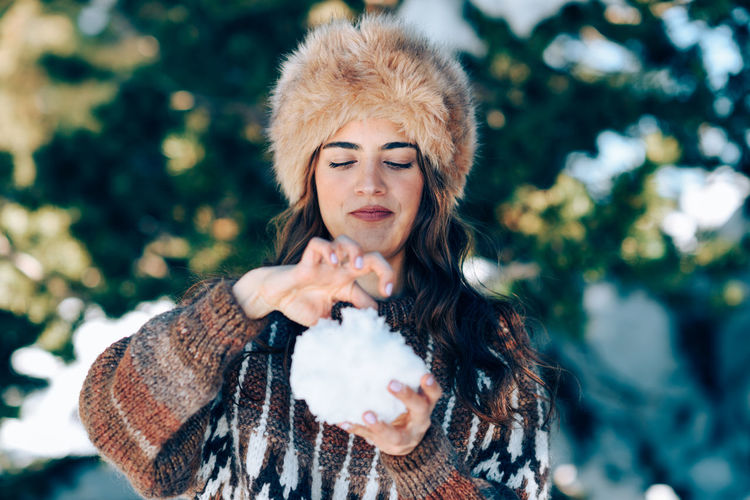 Young woman holding snow while standing outdoors