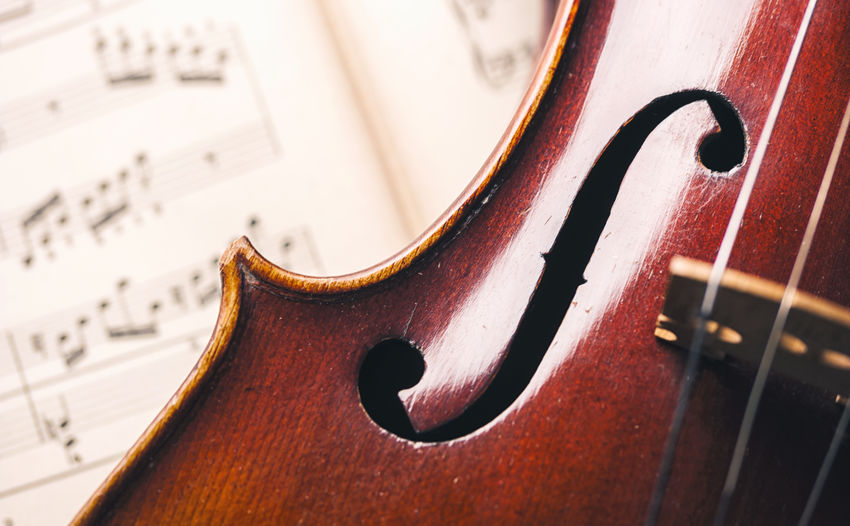 Close-up of a vintage violin with musical notes in the background Antique Classical Music Music Sound String Wood Cello Classical Close-up Harmony Indoors  Instrument Luxury Melody Music Is My Life Musical Musical Instrument Musical Instrument String No People Note Orchestra Paper Sheet Stradivarius Violin