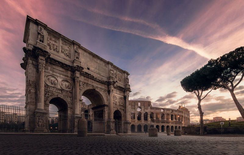 Colosseum with the arch in rome at colorful sunrise panorama Architecture History The Past Arch Sky Built Structure Cloud - Sky Building Exterior Travel Destinations Tourism Sunset Nature Travel Monument City Triumphal Arch Ancient No People Outdoors Ancient Civilization Arched