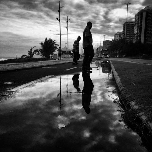 Reflection of people in puddle