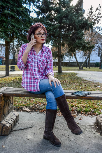 Full length of young woman talking on phone while sitting on bench at park
