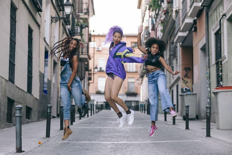 Full length of female friends jumping on street in city