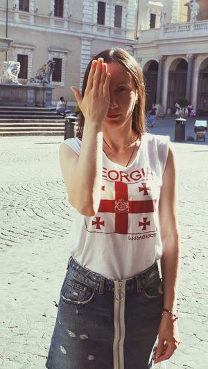 Midsection of woman with arms raised standing in city