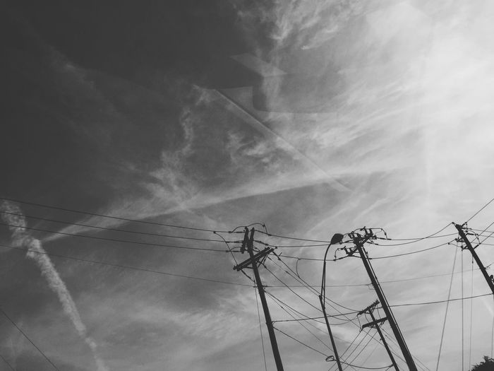 Low angle view of silhouette electric poles against sky